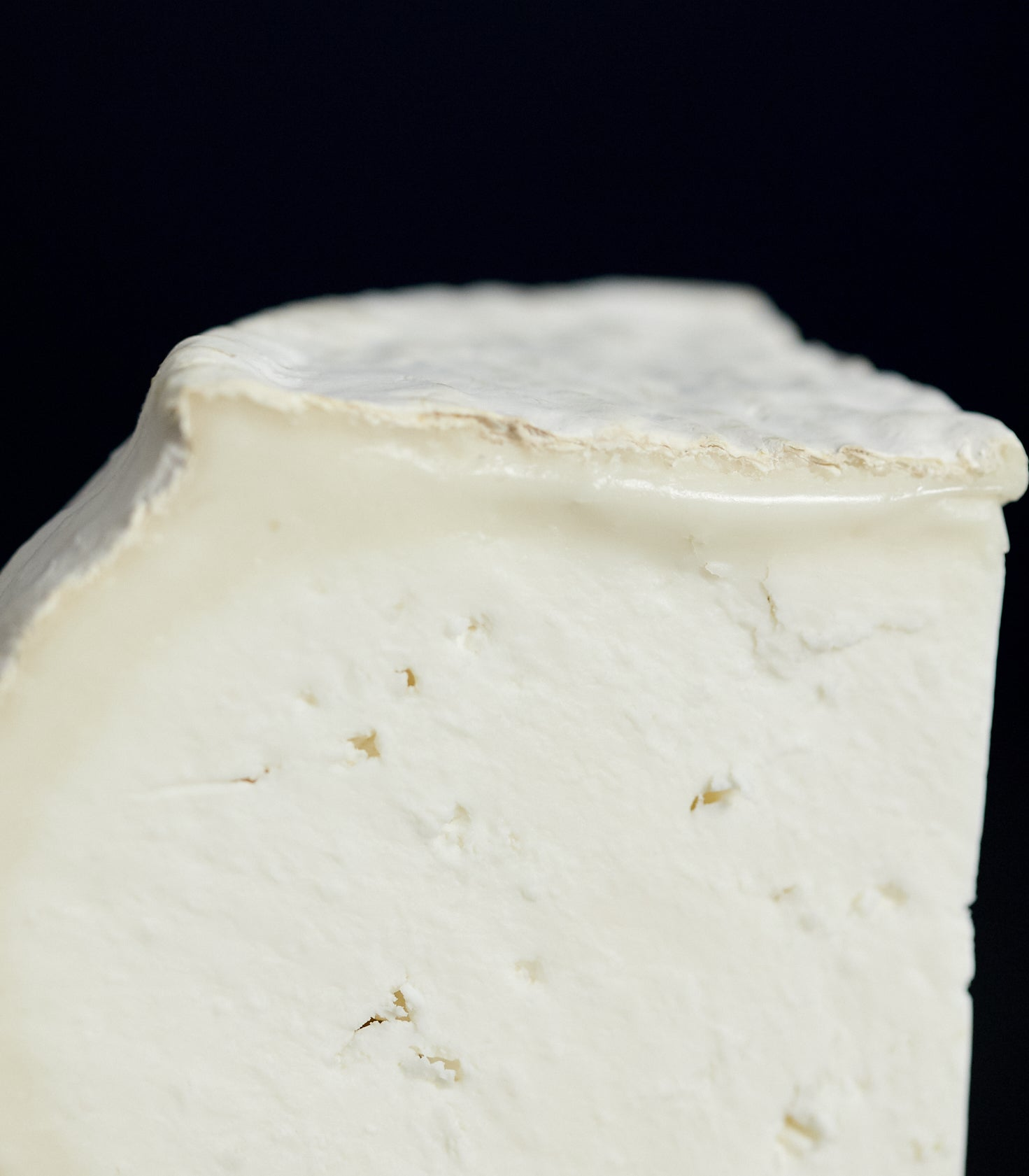 Close up of a cut piece of Ticklemore vegetarian goat's cheese showing the bloomy, natural rind and white, chalky paste