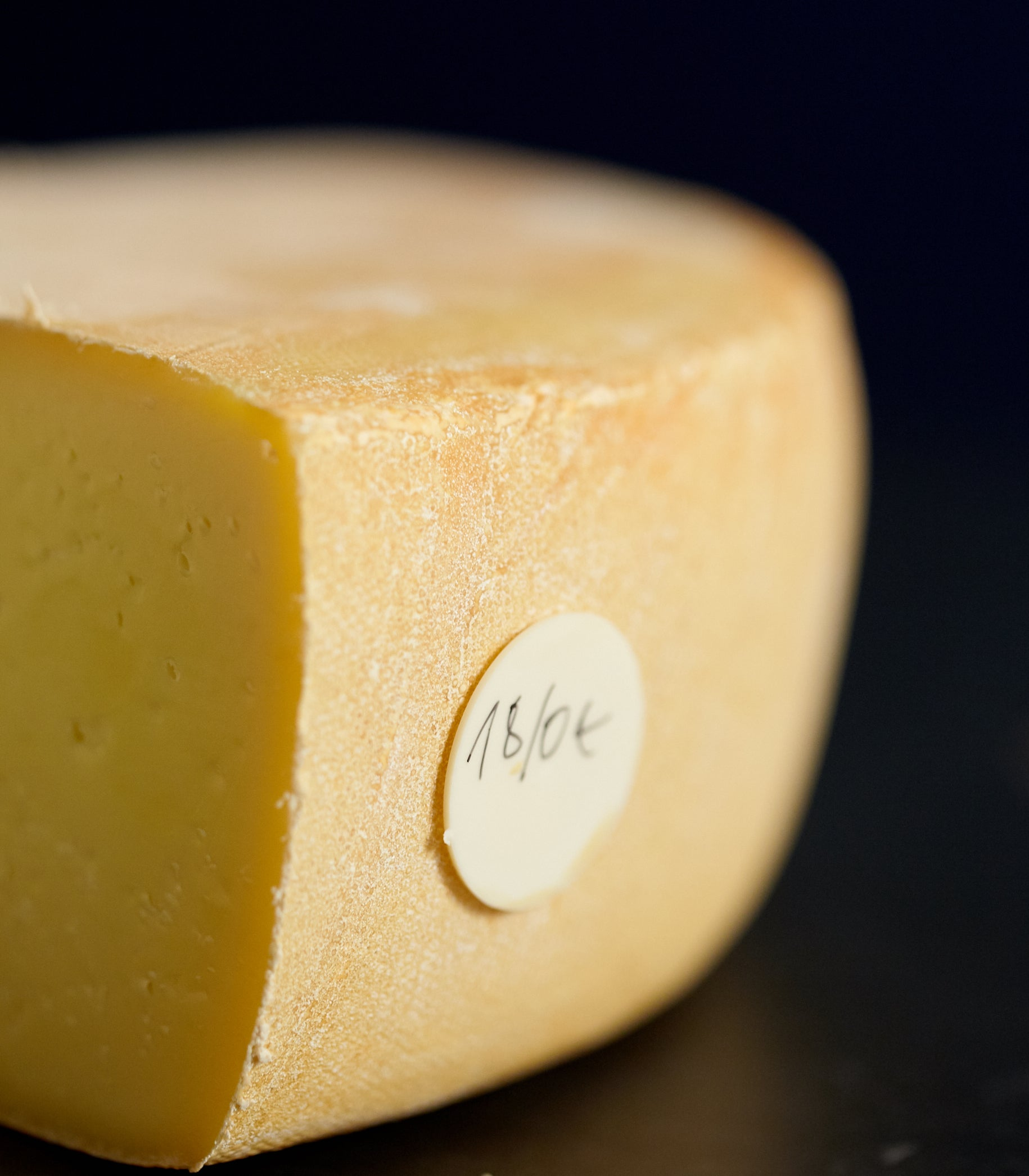 Close up of a cut piece of Raclette-style Ogleshield cheese, showing the firm paste, orange-pink rind and date tag
