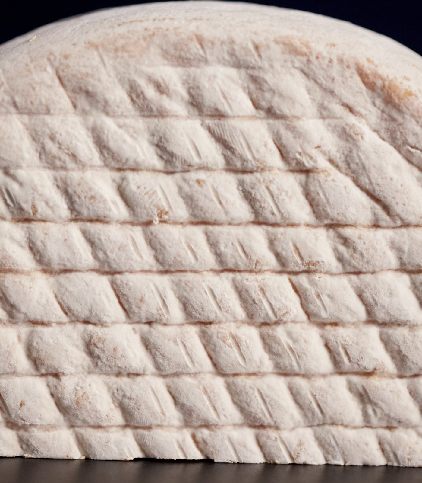 Close up of a Gubbeen semi-soft washed rind cow's milk cheese, showing the patterned rind