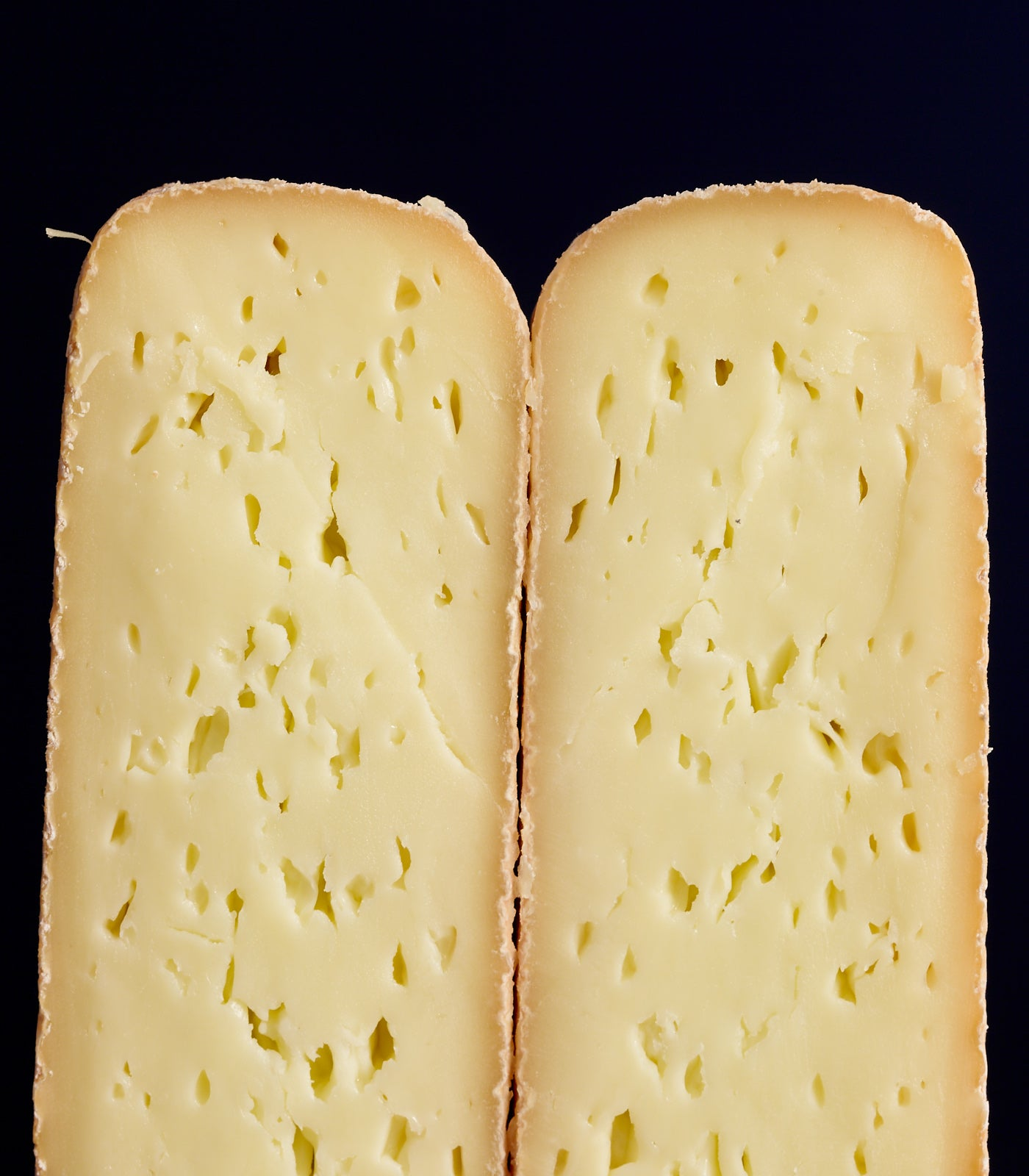 Cross-section of a whole Durrus washed rind cow's milk cheese, showing the soft, creamy paste with tiny holes