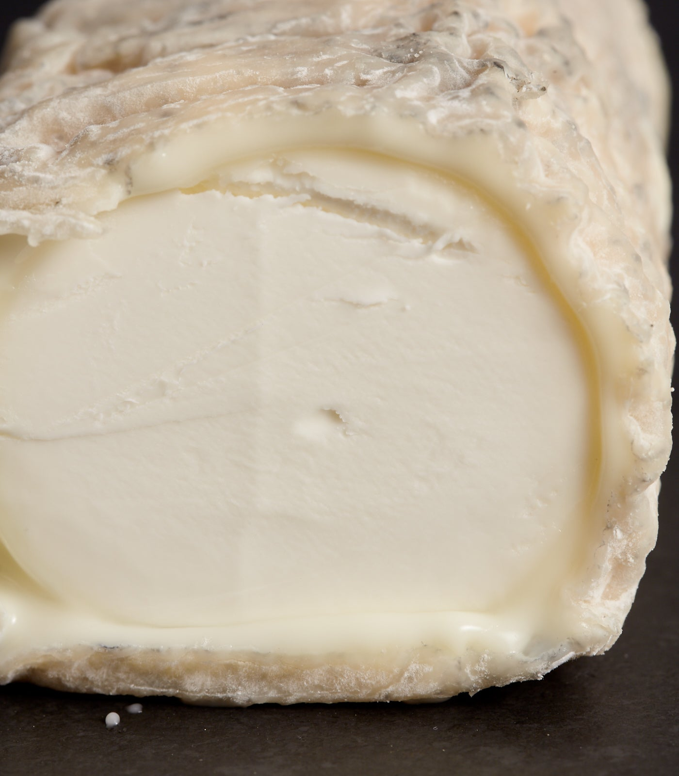 Close up of the cross-section of Innes Log goat's cheese, showing the dense white paste and unctuous breakdown at the pinky-grey wrinkly rind