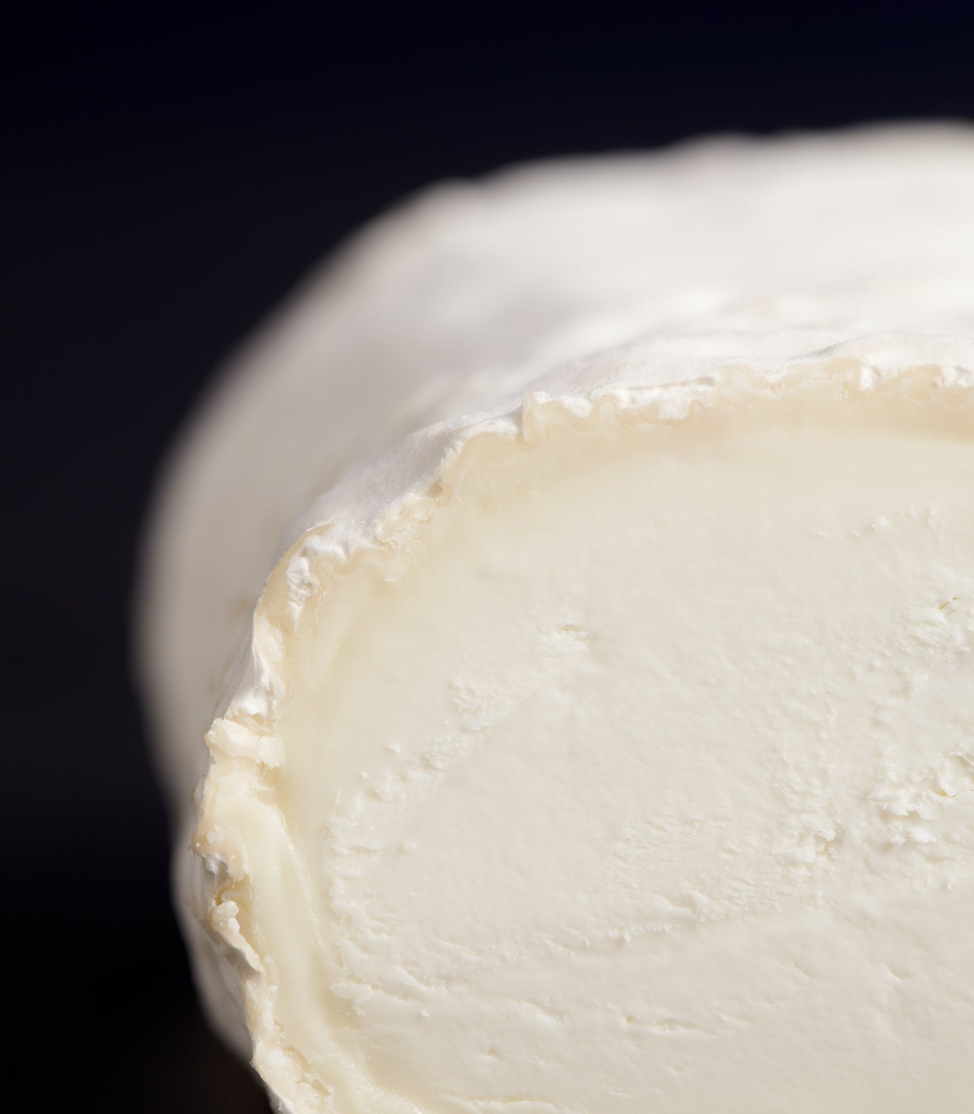 Close up of a cut log-shaped Ragstone goat's milk cheese with delicate smooth white rind and a dense paste