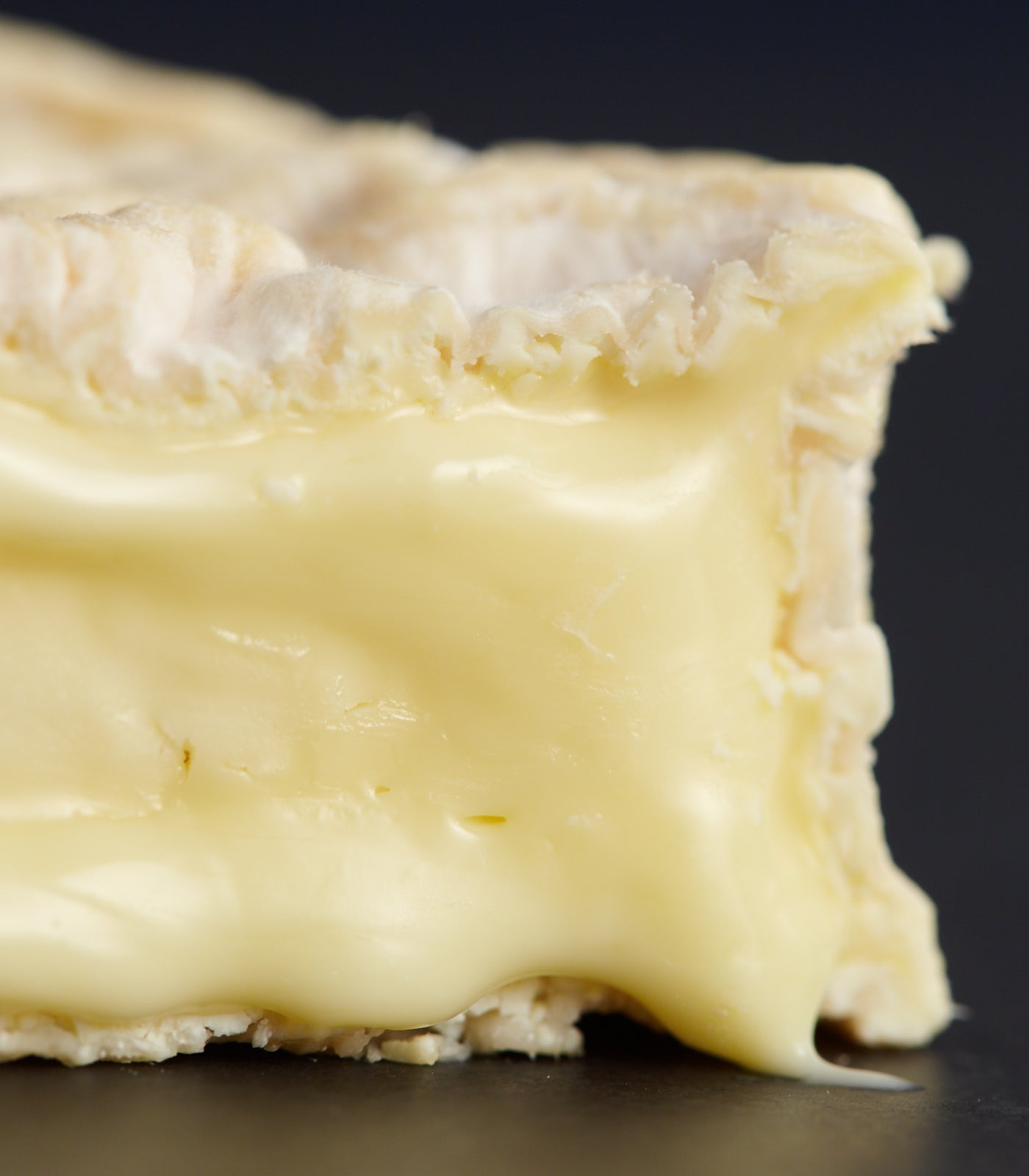 Close up of cut Camembert-style Tunworth cheeses with a soft rind, and creamy, oozing, unctuous paste