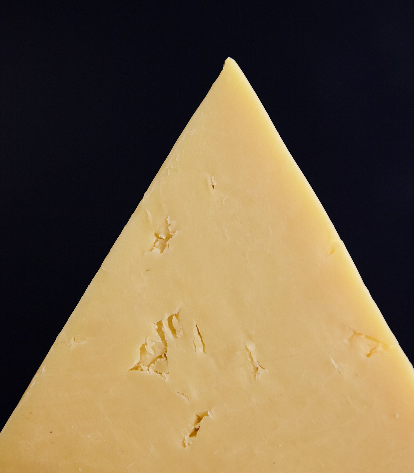 Close up of a cut piece of Lincolnshire Poacher Cheddar cheese, showing the smooth-textured, Comté-like paste