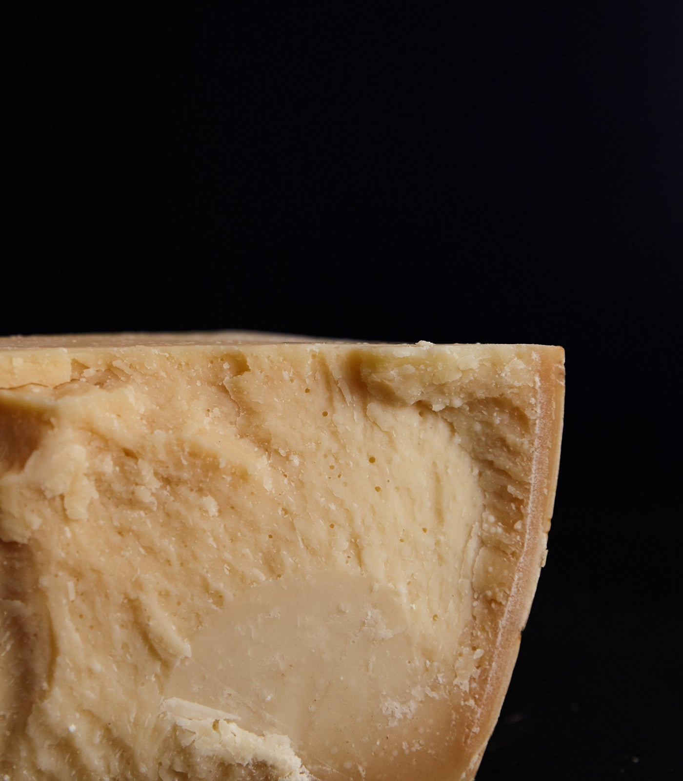 A tower of whole and various cut pieces of Parmigiano San Pietro 2659 cheese showing the print-covered rind and hard, dense, creamy paste    Close up of a cut piece of Parmigiano San Pietro 2659 cheese showing the hard rind and dense, creamy paste