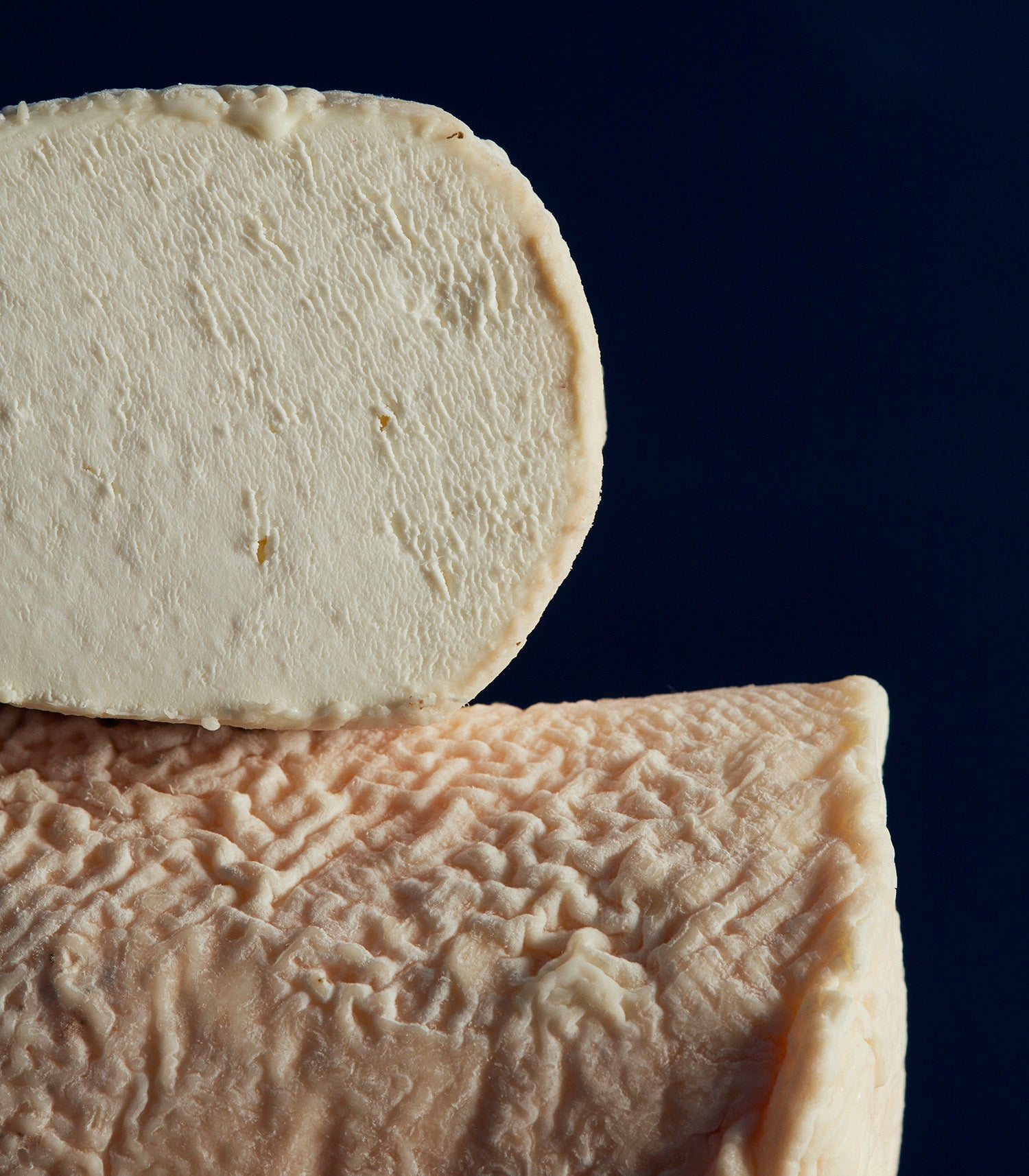 Close up of a cross-section of St Tola goat's cheese, showing the delicate, mould-flecked, pinky-coloured, wrinkly rind and dense, creamy paste