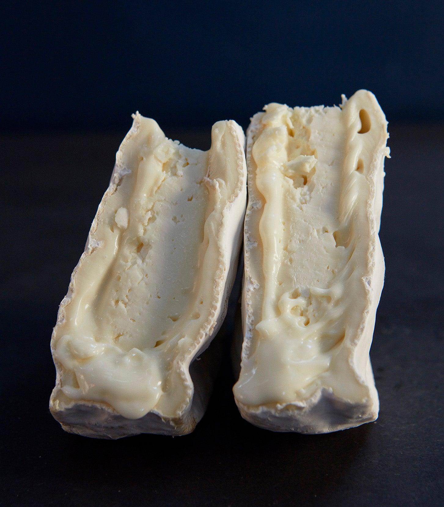 Two cuts of Wigmore vegetarian sheep's cheese, showing the creamy, soft paste beneath the natural, white rind, which is firm and chalky at the centre