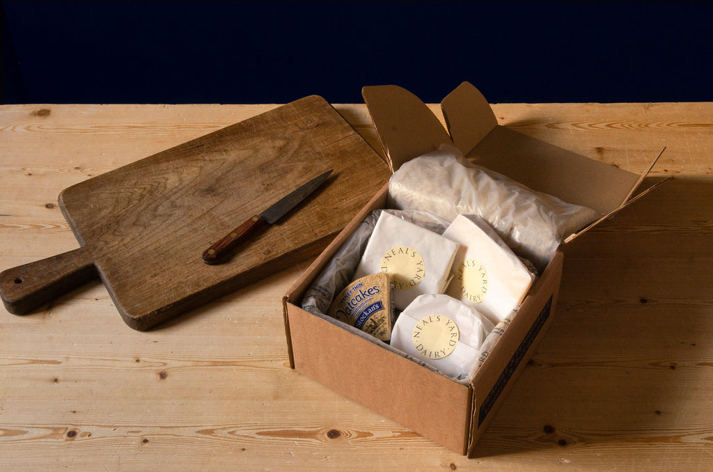 Neals Yard Dairy selection box insulated with a wool liner containing pieces of wrapped cheese