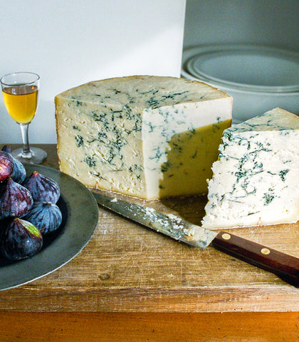 Cheese board with a plate of figs, a glass of white wine and a knife, that has been used to cut a small piece of Colston Bassett Stilton from a larger piece