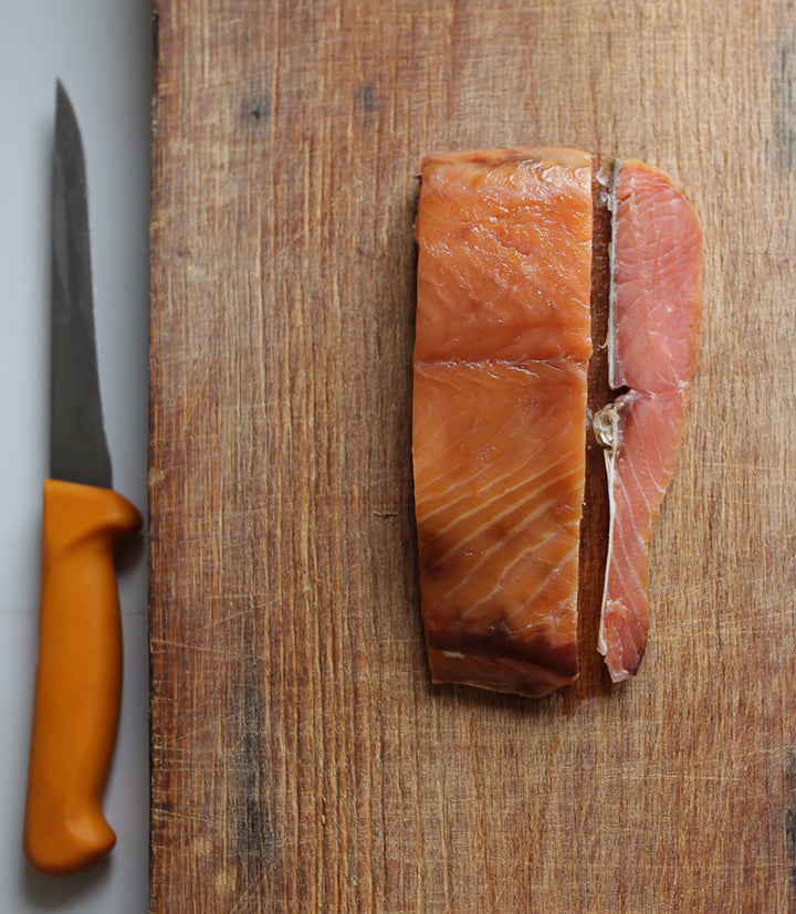 A piece of wild, Irish, traditionally-smoked salmon on a chopping board