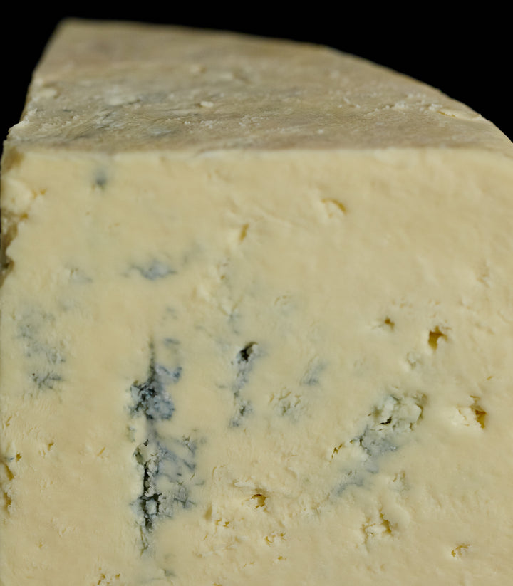 Close up of a cut piece of Devon Blue vegetarian cow's milk cheese, showing the delicate blue veining and crumbly, buttery texture