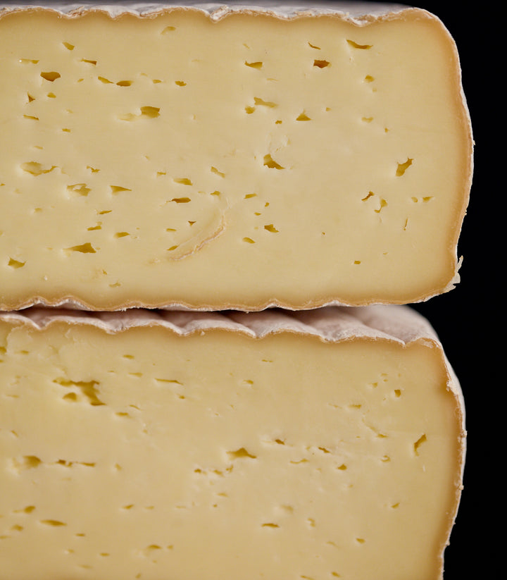 Cross-section of a whole Gubbeen semi-soft washed rind cow's milk cheese, showing the patterned rind and creamy-coloured paste
