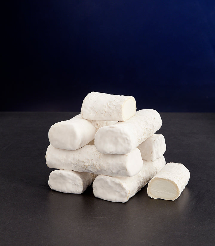Small tower of whole and cut log-shaped Ragstone goat's milk cheeses with a white mould-covered, smooth rind and dense paste