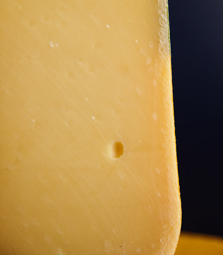 Close up of a cut piece of Coolea Gouda-like cow's miIk cheese, showing the rind and firm, smooth, closely textured paste
