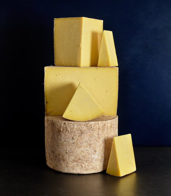 Range of whole and smaller cut pieces of clothbound Pitchfork Cheddar cheese showing whole cheeses and the dense, creamy paste