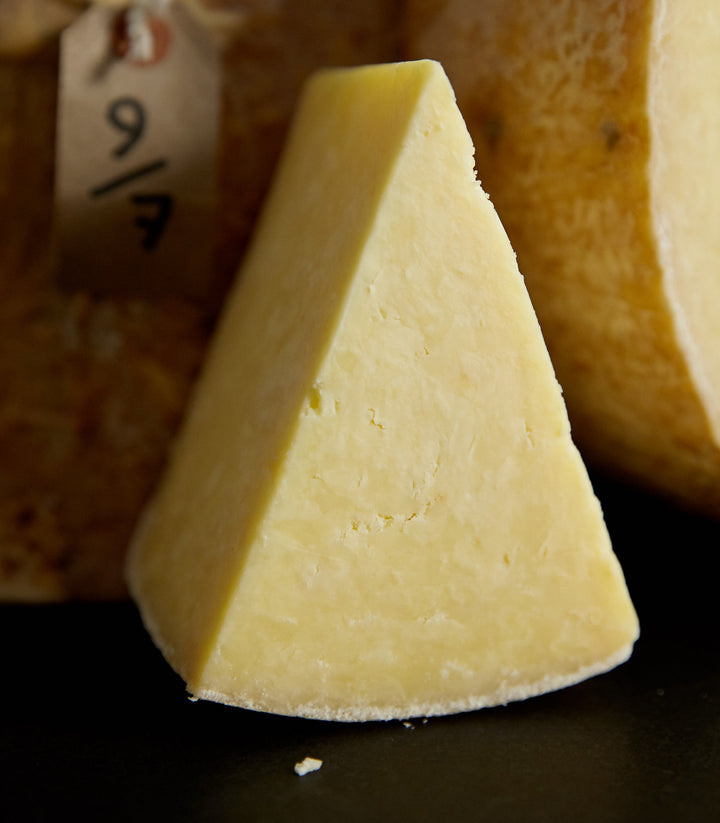 Close up of a cut piece of Kirkham's Lancashire cheese in front of some larger cuts, showing the crumbly textured paste