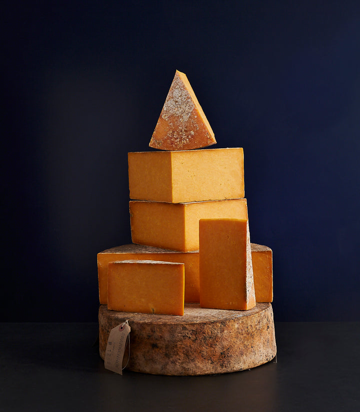 Tower of whole and cut pieces of clothbound Mature Sparkenhoe Red Leicester cheese