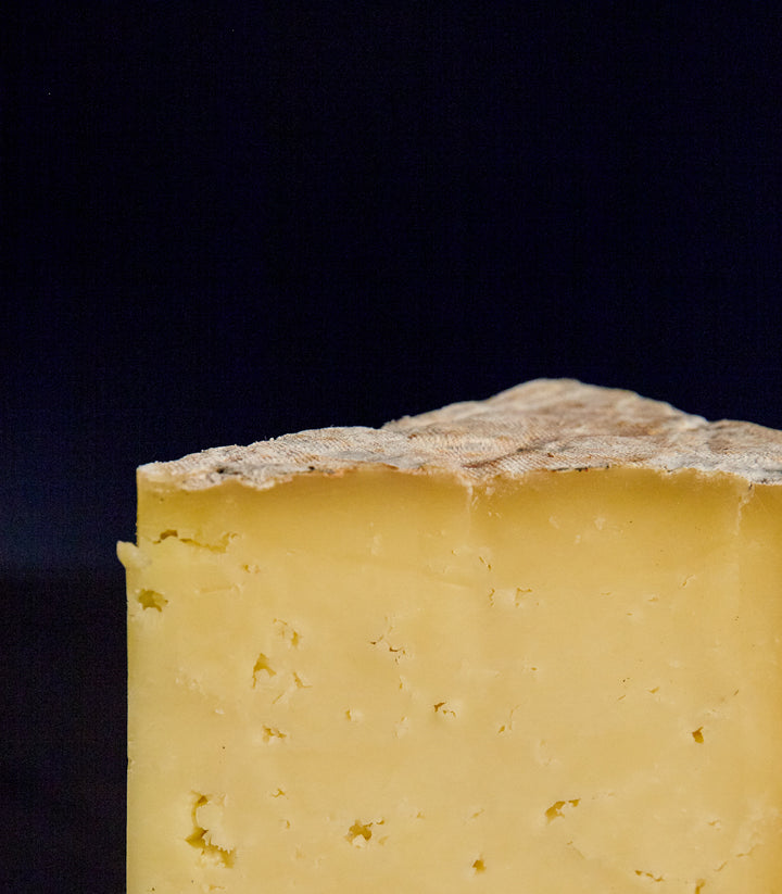 Close up of a cut piece of Whin Yeats Wensleydale raw cow's milk cheese showing the golden-coloured buttery, crumbly paste and the rind