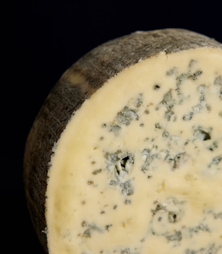 Close up of a cut piece of Cashel Blue vegetarian cow's milk cheese, showing the blue veining, delicate natural rind and rich, buttery paste