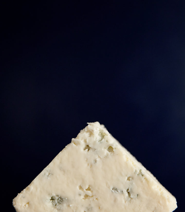 Close up of a cut piece of Beenleigh Blue vegetarian sheep's cheese with delicate blueing and moist but crumbly texture