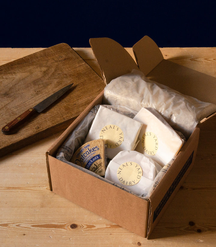 Neal's Yard Dairy Selection Box with wool liner for insulation and containing cut pieces of cheese wrapped in waxed paper