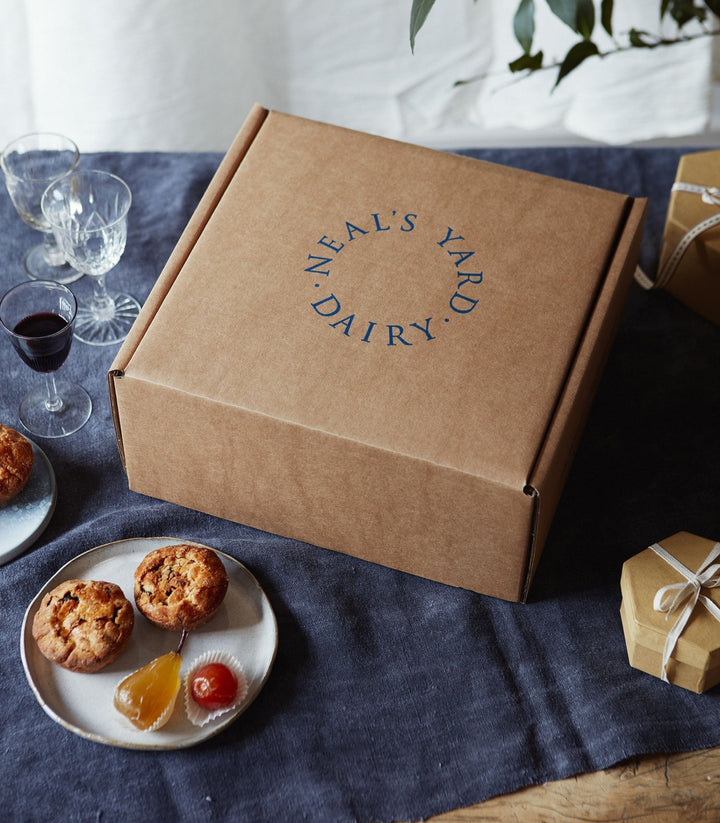 Neal's Yard Dairy cardboard packing box for cheese delivery on a linen tablecloth with wine and cookies