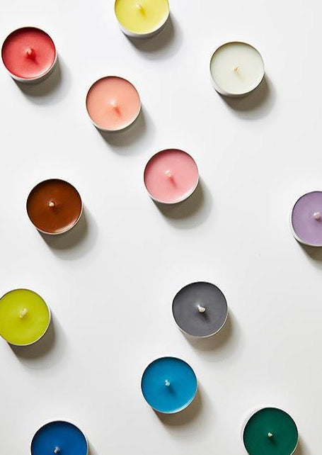 Tea light candles arranged in rainbow colors.