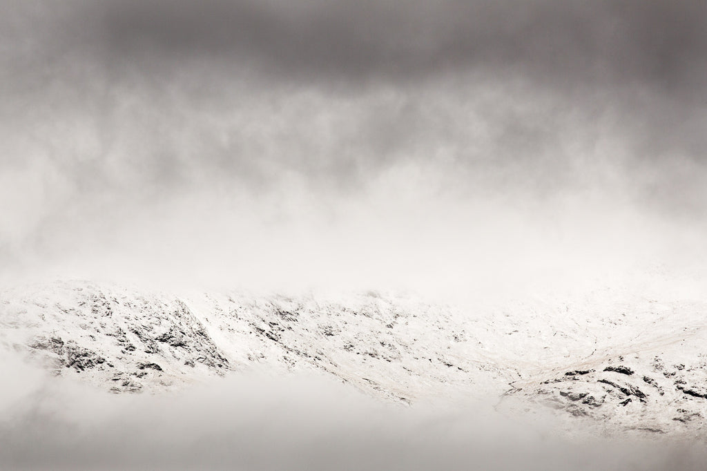 Snowy Scottish mountains poking through the mist in an almost monochromatic photograph