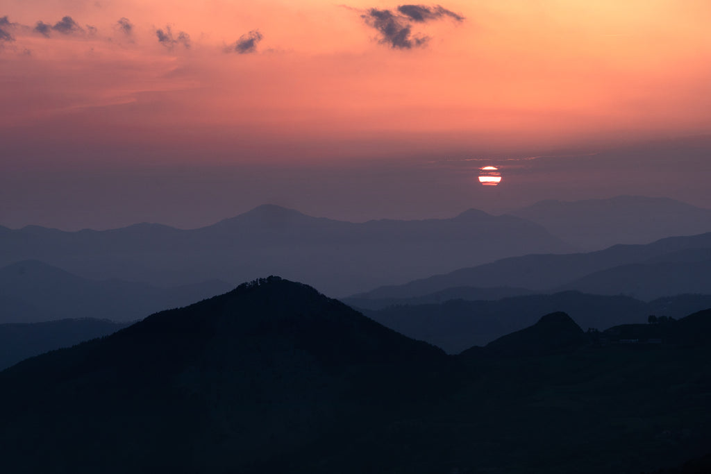 Dreamy sunset over the Maritime Alps, a globular sun in a red sky over smoky mountain ridges