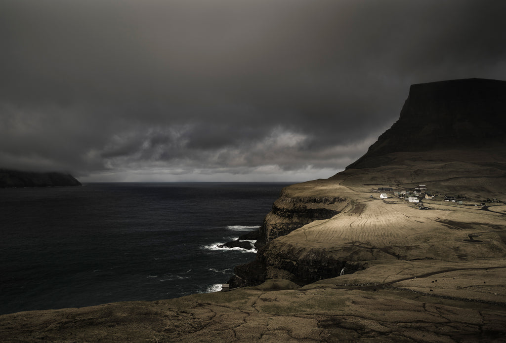 A shaft of light illuminates a remote village on the Faroe Islands. The sky is stormy and waves can be seen breaking on the rocky shore below the cliffs