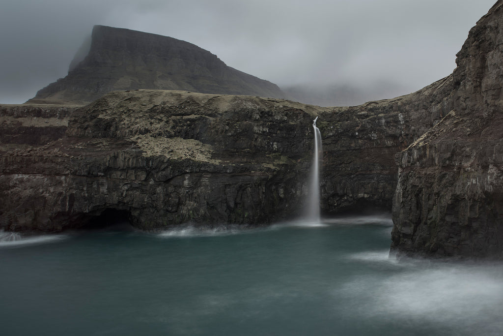 Spectacular waterfall dropping from a cliff on the Faroe Islands into a turquoise sea, made milky by using a slow shutter speed technique.