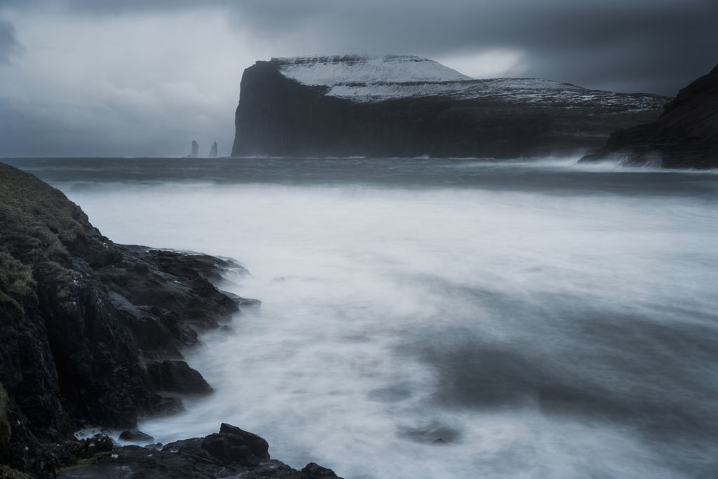 Dramatic landscape of the cliffs and sea of the Faroe Islands in moody blue and grey tones.  Snowcapped hillsides and churning sea.