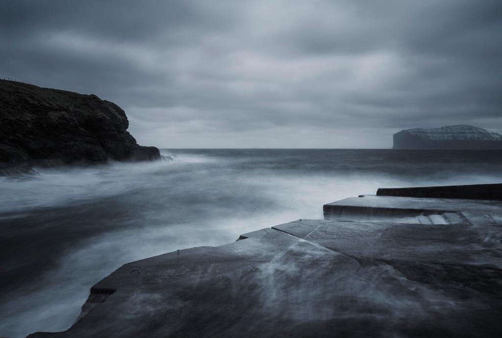Moody  brooding photograph in blue and grey tones showing a remote harbour in the Faroe Islands, snowy capped cliffs in the distance and a wild churning sea.