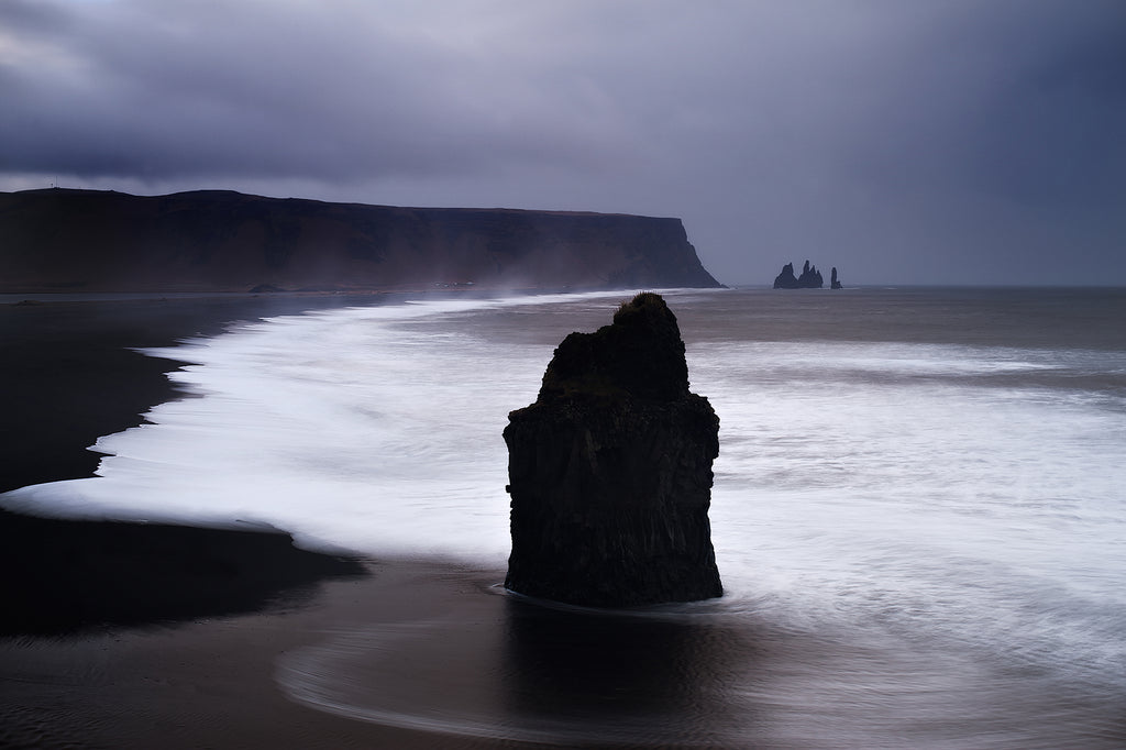 Dramatic and moody photography in purple and black tones of a rock stack in a wild sea off the southern coast of Iceland