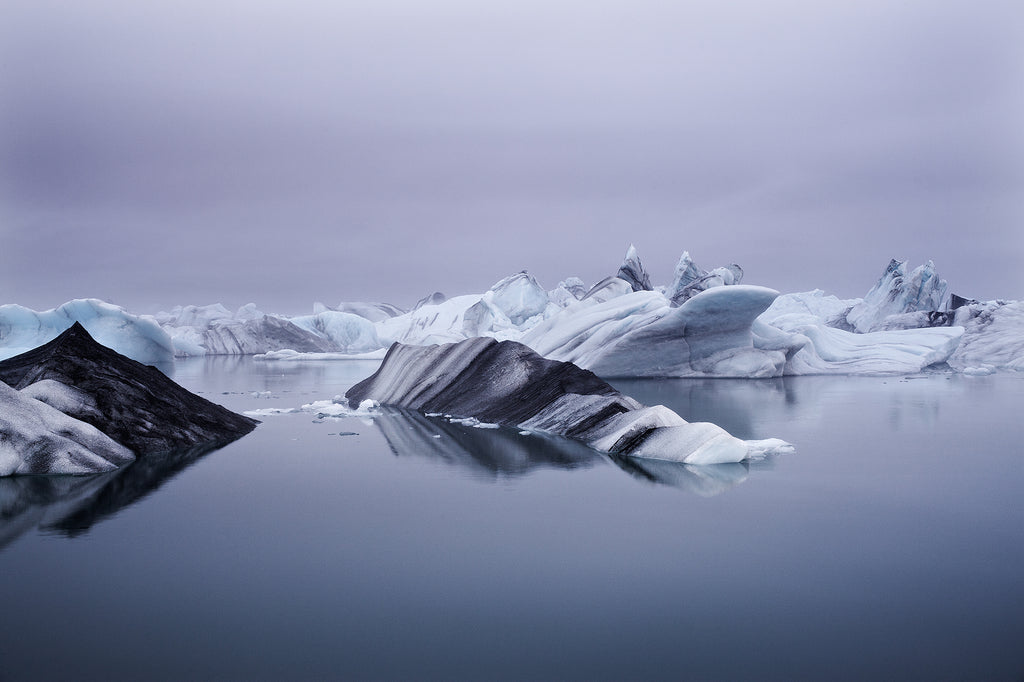 Gorgeous landscape photograph of icebergs floating in a glacial lagoon in Iceland. The tones range from blue to mauve to black.  Very serene.