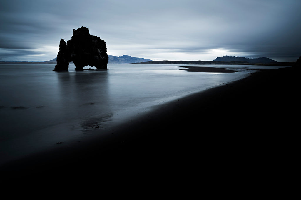 A dramatic and moody landscape photograph of The Drinking Dragon' a large rock structure off the coast of Iceland. Black, blue and grey tones