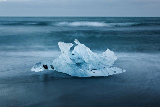 Gorgeous photograph of an iceberg remnant on the south coast of Iceland, awash with incoming waves.  Sumptuous blue tones and light