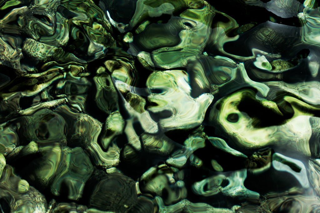 Very quirky green abstract photograph of the Ligurian sea, showing face like shapes formed in the interplay between surface tension and the sea bed