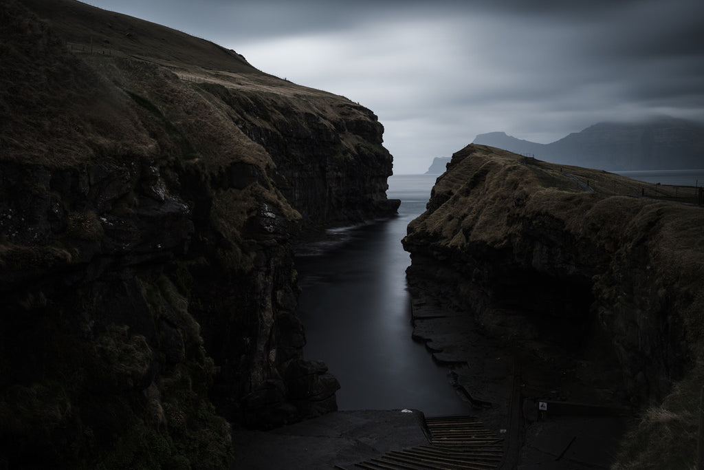 A deep brooding cleft acts as a natural harbour in the Faroe Islands, atmospheric and moody with steps leading down to the water