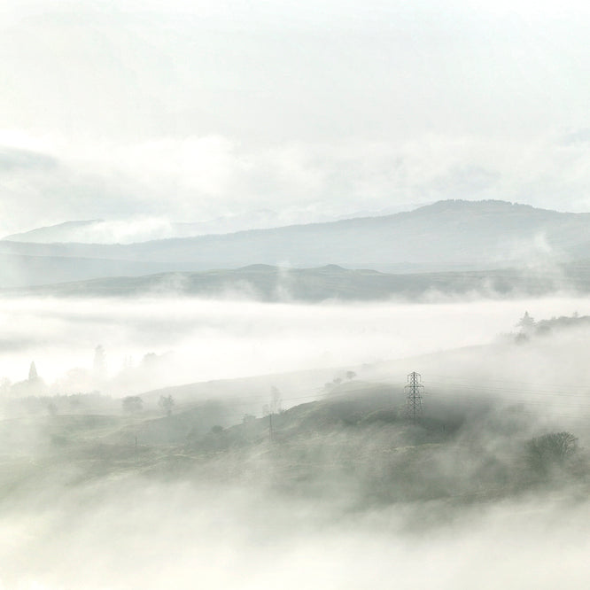 Misty Scottish hilly landscape, with a pylon shrouded in mist and many ridge lines receding into the distance