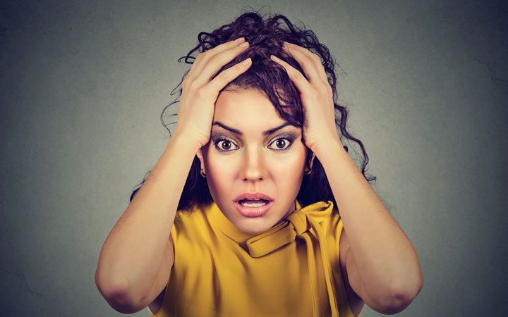 stressed worried woman with hands on head