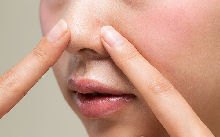 a woman with beautiful skin is pointing at her nose