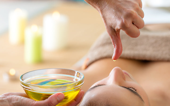 aromatic oil in glass bowl next to woman at ayurveda massage.