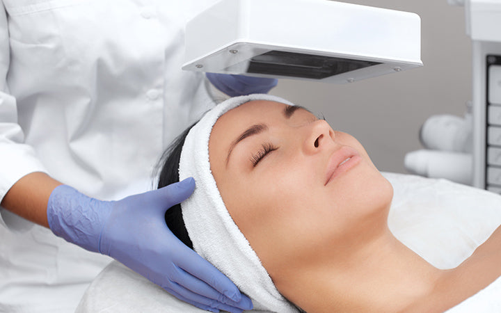 cosmetologist using wood lamp for diagnosis of skin condition
