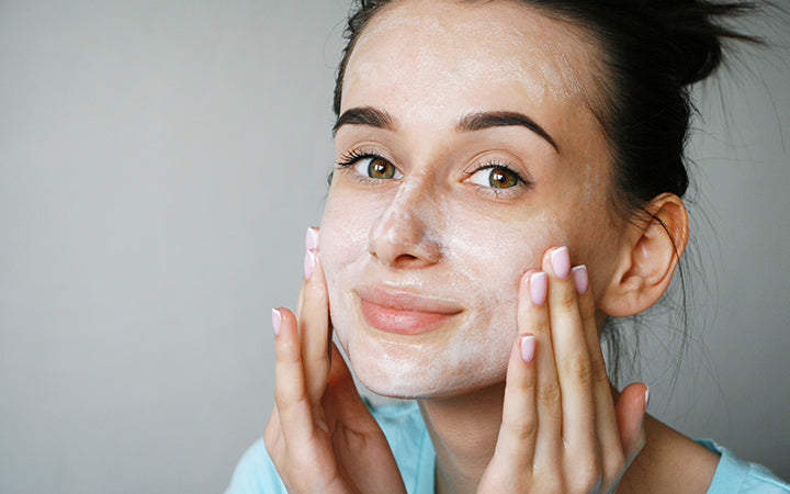 girl cleansing uneven skin on face