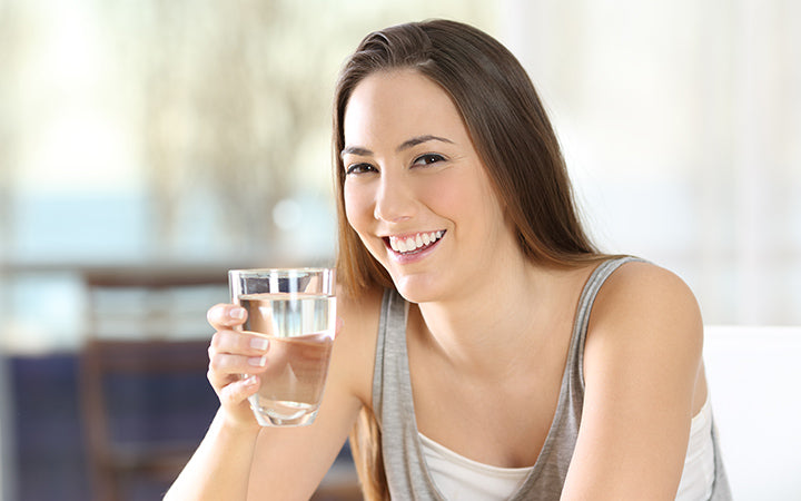 happy woman posing holding a glass of water at home