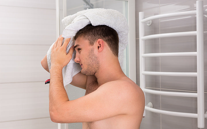 man dries his wet hair with a clean towel