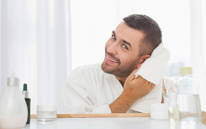 man drying off his hair while looking into the mirror