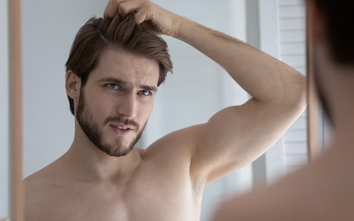 man with dry hair looking in mirror