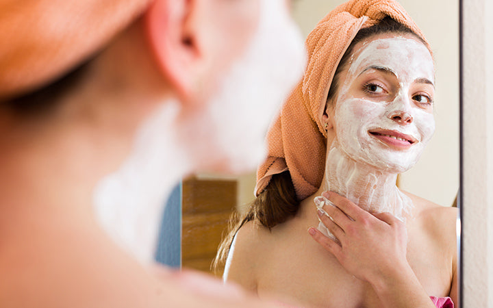 woman applying face pack infront of mirror